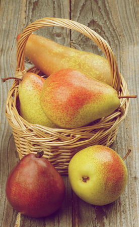 retro styled: Arrangement of Red, Yellow and Conference Pears in Wicker Basket closeup on Rustic Wooden background. Retro Styled Stock Photo