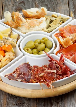 cured ham: Arrangement of Spanish Snacks with Various Cheeses, Jamon, Cured Ham, Green Olives and Bread Sticks on Serving Plate closeup on Wooden background Stock Photo