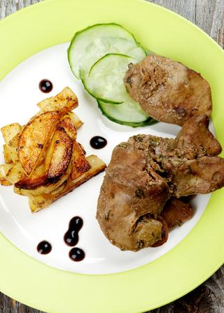 higado de pollo: Pollo asado delicioso h�gado Dispuestos con los palillos de la patata a la parrilla, pepino y salsa de bals�mico en la placa verde en el fondo de madera r�stica. Vista Superior Foto de archivo