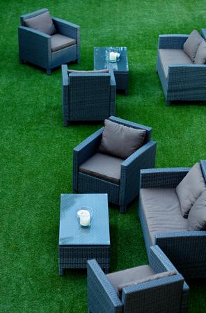 Moderne Lounge-Zone mit Korbstühlen mit bequemen Kissen und Tische auf perfektem grünen Gras Im Freien Lizenzfreie Bilder