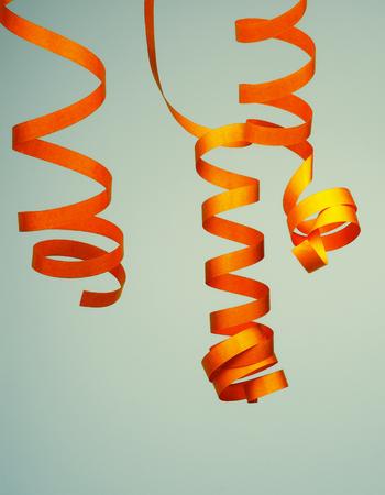 serpentinas: Tres de oro encrespadas Party Streamers aislados en Azul-Gris entonó el fondo Foto de archivo