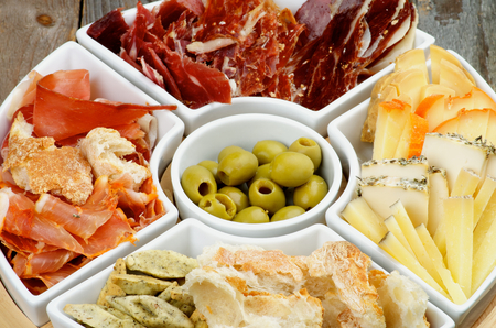 cured ham: Serving Plate with Various Spanish Cheeses, Jamon, Cured Ham, Green Olives and Bread Sticks closeup on Wooden background Stock Photo