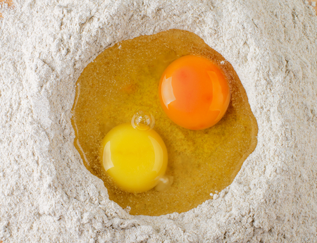 doughy: Two Light Yellow and Dark Yellow Egg Yolks into Heap of Whole Wheat Flour closeup. Top View