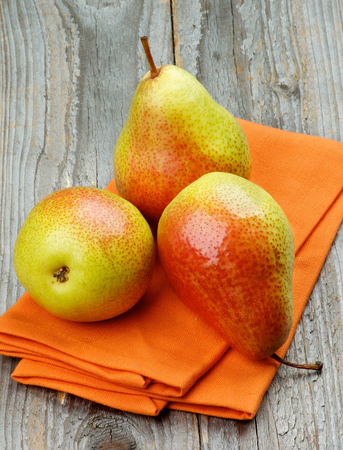 green yellow: Three Ripe Yellow and Red Pears on Orange Napkin closeup on Rustic Wooden background