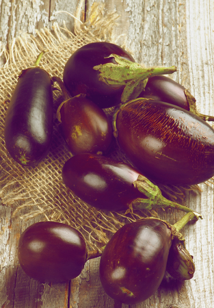 retro styled: Fresh Ripe Small Eggplants on Sackcloth on Rustic Wooden background. Retro Styled Stock Photo