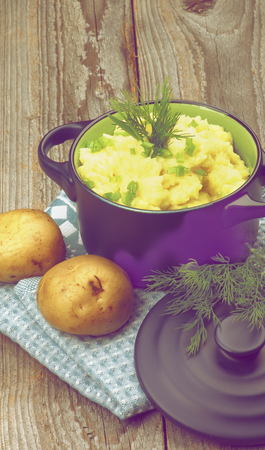 dark blue: Homemade Mashed Potato with Dill and Spring Onion in Dark Blue Casserole with Lid on Rustic Wooden background. Retro Styled