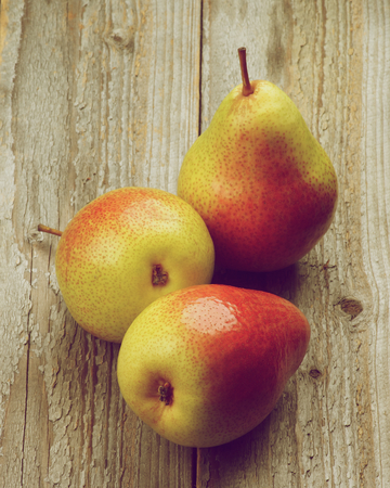 retro styled: Three Fresh Raw Yellow and Red Pears isolated on Rustic Wooden background. Retro Styled Stock Photo