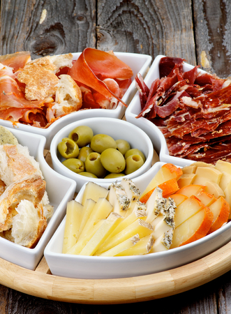 cured ham: Arrangement of Spanish Snacks with Various Cheeses, Bread Sticks, Jamon, Cured Ham and Green Olives on Serving Plate closeup on Wooden background