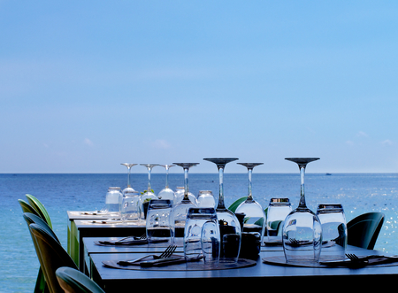 stemware: Elegant Served Restaurant Tables with Various Stemware and Silverware on Terrace in Shadow on Sea Coast Outdoors