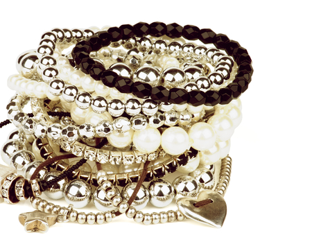 retro styled: Pile of Various Pearl, Silver and Black Jewelry Gems Bracelets closeup on white background. Retro Styled