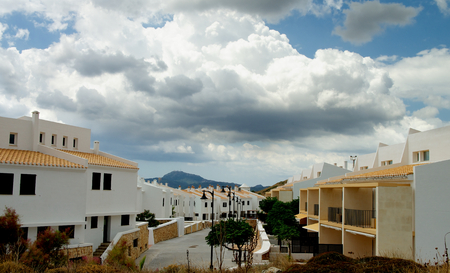 menorca: Classic Small Menorca Urbanization with White Houses under Cloudy Skies Outdoors. Balearic Islands