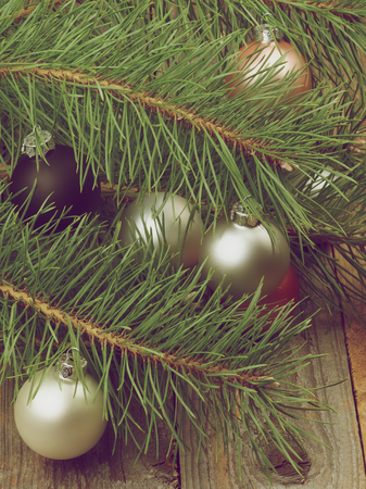 solver: Christmas Decoration with Solver, Black and Pink Baubles into Fluffy Green Pine Branches closeup on Rustic Wooden background. Retro Styled Stock Photo