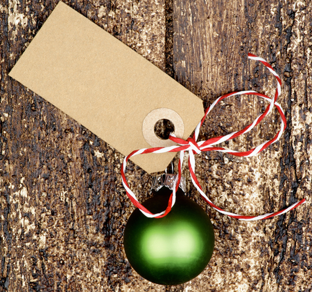 annotation: Christmas Decoration with Green Bauble, Striped Bow and Gift Card Note closeup on Textured Wooden background