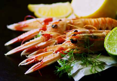 prepared shellfish: Delicious Grilled Langoustines  on Newspaper with Lime and Lemon closeup on Dark Wooden background. Focus on Animal Eyes on Foreground