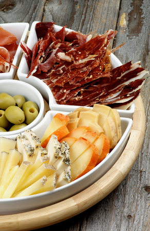 cured ham: Various Spanish Snacks with Goat Cheeses, Jamon, Cured Ham and Green Olives on Serving Plate closeup on Wooden background Stock Photo