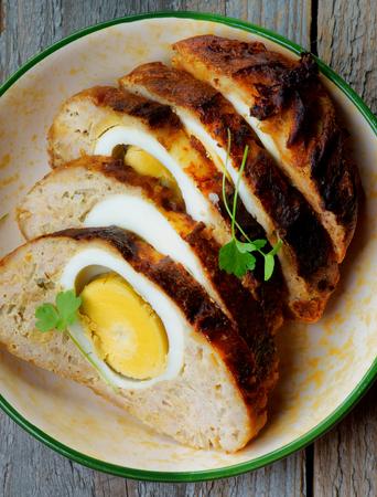 pastel de carne: Delicioso Slised Pastel de carne relleno con huevos hervidos en taz�n de fuente de cerca sobre fondo de madera r�stica