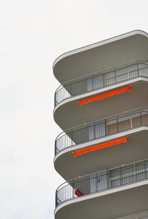 building feature: Modern Apartment Building with White Facade and Balcony with Orange Details closeup on Cloudy Sky background Outdoors Stock Photo