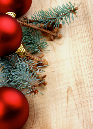 corner border: Corner Border of Blue Spruce Branch with Fir Cones and Red Baubles closeup on Wooden background