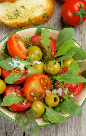 rustic food: Arrangement of Tomatoes Salad with Arugula, Olives and Greens in Bowl and Garlic Bread closeup on Rustic Wooden background. Top View Stock Photo