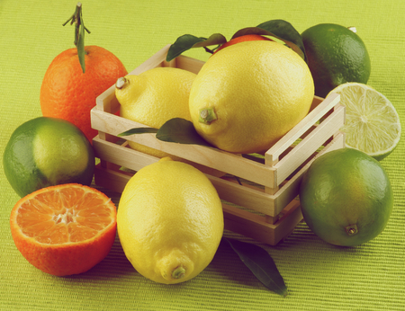 retro styled: Heap of Various Citrus Fruits with Lemons, Oranges, Tangerines and Limes Full Body and Halves in Wooden Box closeup on Green Napkin background. Retro Styled