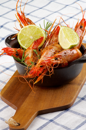 prepared shellfish: Delicious Roasted Shrimps in Cast Iron with Lime and Rosemary on Wooden Cutting Board closeup on Checkered Napkin background Stock Photo