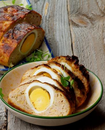 albondigas: Rebanadas de deliciosa hecha en casa con carne relleno con huevos duros y Verdes en dos Tazón de cerca sobre fondo de madera rústica Foto de archivo