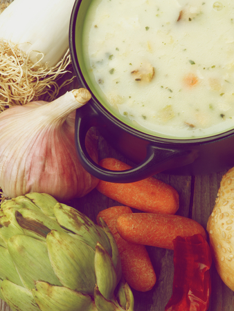 retro styled: Healthy Artichoke Creamy Soup with Leek, Carrot, Garlic and Cheese in Dark Blue Pannikin closeup on Rustic Wooden background. Retro Styled