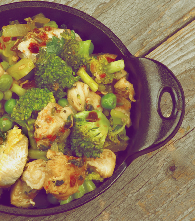 green pea: Homemade Chicken Stew with Broccoli, Bell Pepper and Green Pea in Black Saucepan on Rustic Wooden background. Retro Styled Stock Photo