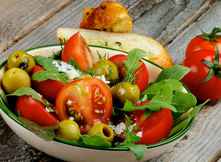 garlic bread: Fresh Tomatoes Salad with Arugula, Olives, Greens, Sea Salt and Garlic Bread isolated on Rustic Wooden background Stock Photo