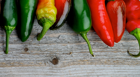 food ingredient: Horizontal Frame of Various Red and Green Habanero and Jalapeno Chili Peppers with Stems on Rustic Wooden background Stock Photo