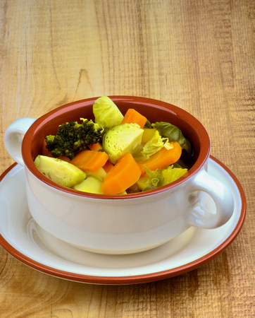 brussels sprouts: Vegetable Rustic Stew with Brussels Sprouts, Broccoli, Carrot, Potato and Leek in Bowl with closeup on Wooden background