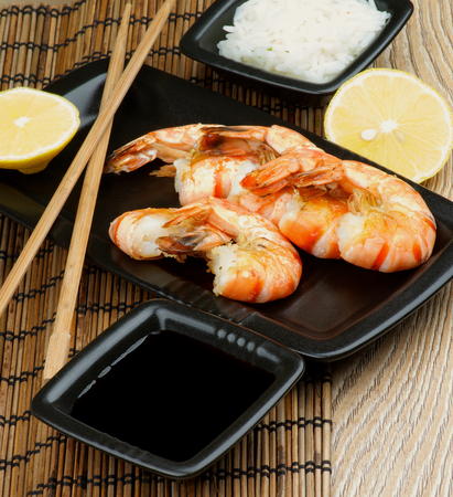 straw mat: Delicious Asian Style Roasted Shrimps with Soy Sauce, Boiled Rice, Lemon and Chopsticks on Straw Mat background closeup