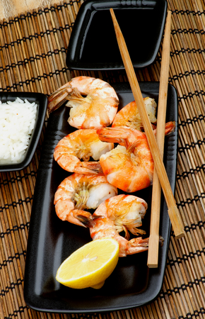 straw mat: Delicious Asian Style Roasted Shrimps with Lemon and Chopsticks, Soy Sauce and Boiled Rice in Square Bowls  on Straw Mat background closeup