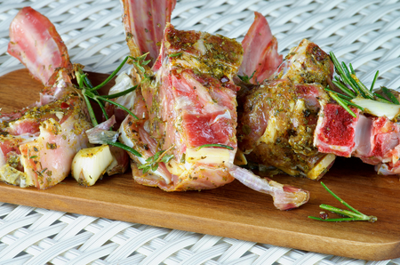 marinade: Delicious Raw Lamb Ribs in Marinade of Herbs and Spices with Rosemary and Garlic Ready to Roast closeup on Wooden Cutting Board Stock Photo