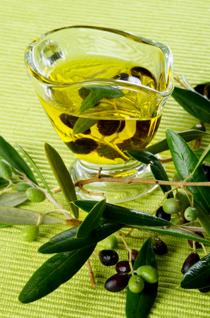 olive green: Olive Oil in Glass Gravy with Raw Green and Black Olives with Leafs closeup on Green Textile background Stock Photo