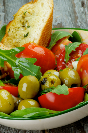 sal: Fresh Tasty Tomatoes Salad with Arugula, Olives and Greens with Garlic Bread in Bowl closeup on Rustic Wooden background