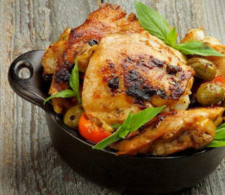 carne de pollo: Crujiente sabroso pollo asado muslos con las aceitunas verdes, tomates y albahaca en Negro Sartén primer en el fondo de madera rústica