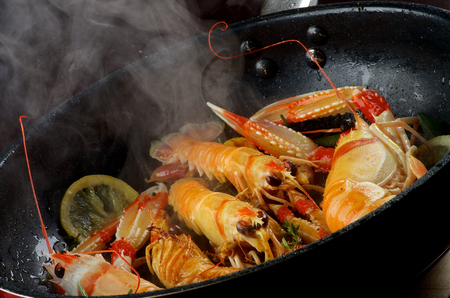 prepared shellfish: Delicious Grilled Langoustines with Lemon and Rosemary Stir-Fried in Cast Iron Pan closeup