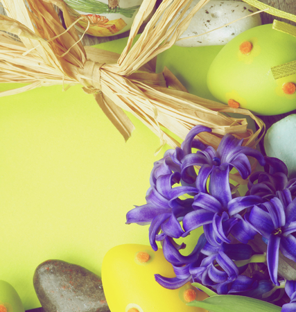 retro styled: Easter Greeting Card with Crocus, Colored Stones, Easter Eggs and Dry Grass with Empty Green Place to Congratulations. Retro Styled Stock Photo
