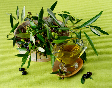olive green: Olive Oil in Glass Gravy with Raw Green and Black Olives with Leafs in Wooden Bowl closeup on Green Textile background Stock Photo