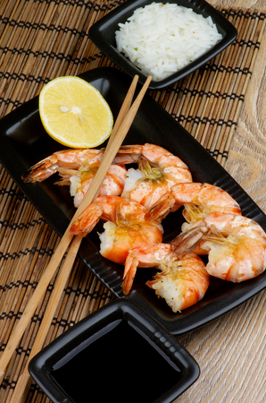 straw mat: Delicious Roasted Shrimps with Lemon and Chopsticks, Soy Sauce and Boiled Rice in Square Bowls on Straw Mat background in Asian Style
