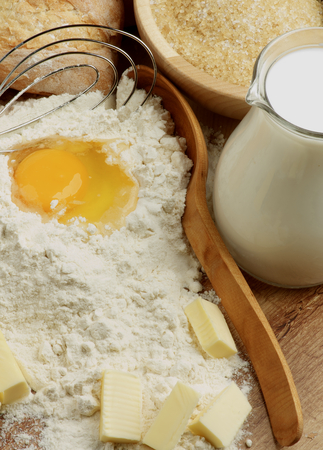 egg whisk: Preparing Homemade Dough with Ingredients, Wooden Spoon and Egg Whisk closeup on Wooden Cutting Board