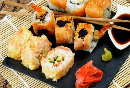 straw mat: Arrangement of Various Maki Sushi with Tempura Crab, Smoked Salmon and Eel with Black Caviar on Stone Plate with Soy Sauce, Ginger and Pair of Chopsticks closeup on Straw Mat background
