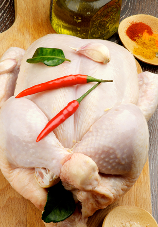 Big Raw Chicken Full Body Trussed and Ready to Roast with Hot Crushed Spices, Chili Peppers, Garlic and Olive Oil closeup on Wooden Cutting Board Stock Photo