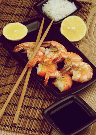 straw mat: Delicious Roasted Shrimps with Soy Sauce, Boiled Rice, Lemons and Chopsticks in Asian Style closeup Straw Mat background