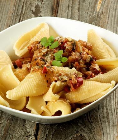 pastas: Deliciosa pasta Conchiglie Gigantes (Giant Pasta Shells) con salsa de carne bolo�esa en el taz�n de fuente blanco Corte transversal en el fondo de madera