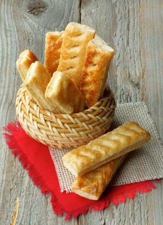 danish puff pastry: Puff Pastry Sticks Sprinkled with Sugar Crystals in Wicker Bowl and Napkins closeup on Wooden background