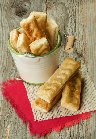 danish puff pastry: Puff Pastry Sticks Sprinkled with Sugar Crystals in White Bucket and Napkins closeup on Wooden background