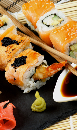 straw mat: Arrangement of Maki Sushi with Smoked Salmon and Eel with Black Caviar on Stone Plate with Soy Sauce, Ginger and Pair of Chopsticks closeup on Straw Mat background Stock Photo