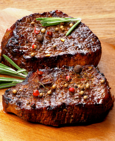beefsteaks: Two Gourmet Roasted Beef Steaks with Peppercorns and Coriander Seeds and Rosemary closeup on Wooden Plate